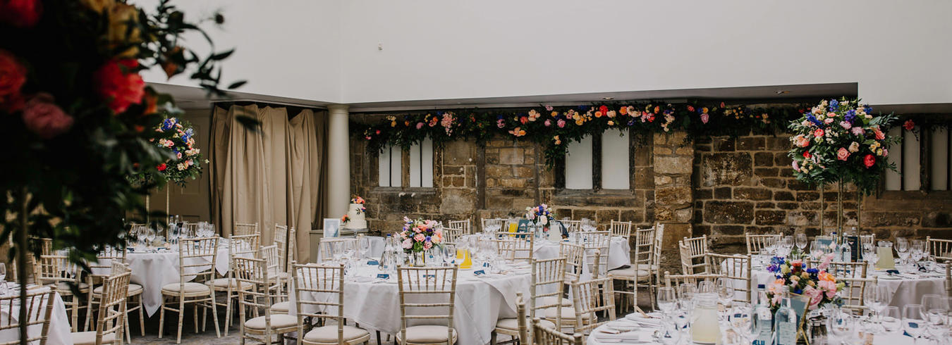 a photo of a wedding reception with oval tables and flowers