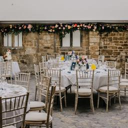 this is a photo of a wedding reception with flowers and stone walls
