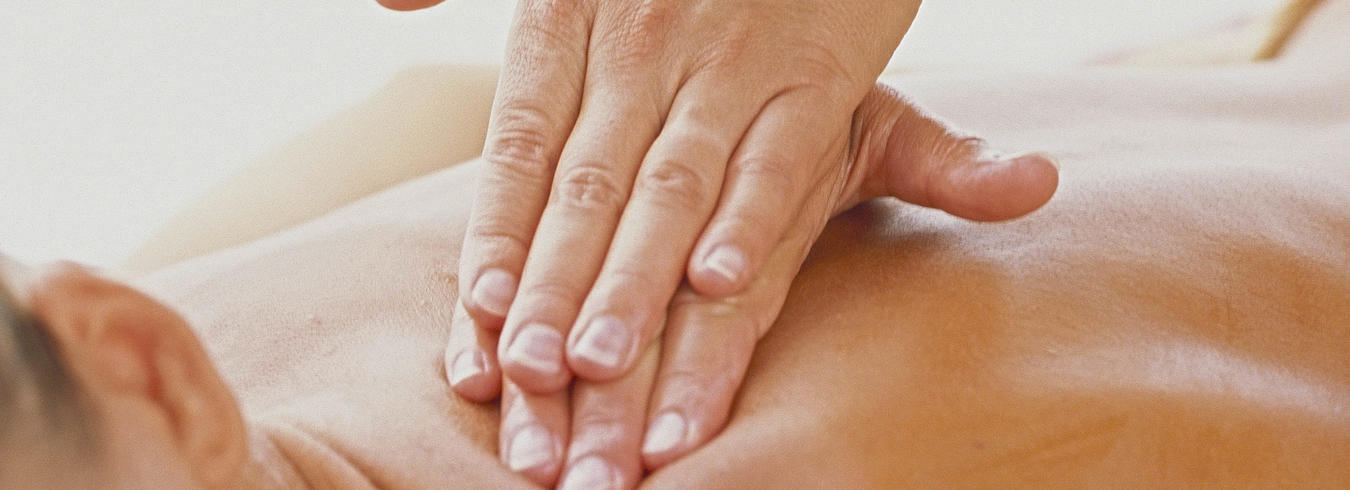a photo of a lady giving a back massage to a guest