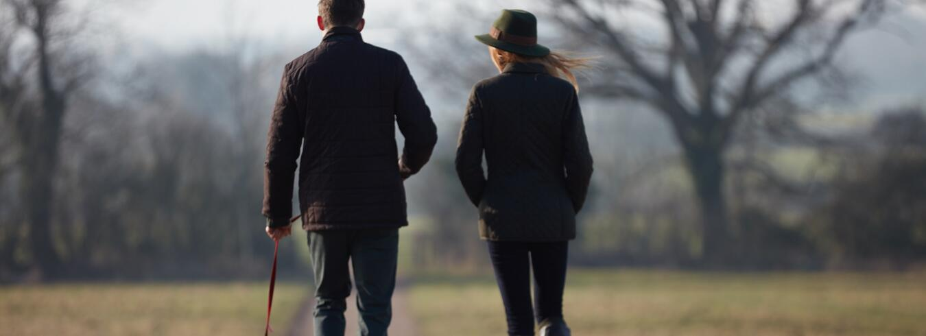 a couple Walking through the Cotswolds countryside with their dog