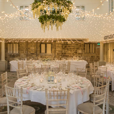 this is a photo of a wedding reception with white round tables and fairy lights in the ceiling