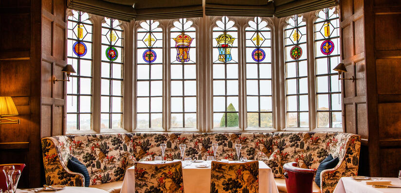 a photo of the restaurant set up for dinner with large stained windows