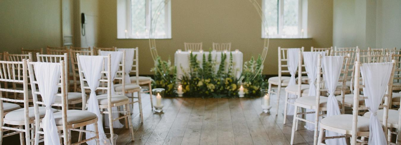 this is a photo of a wedding reception in a church with a white arch and a flower arrangement