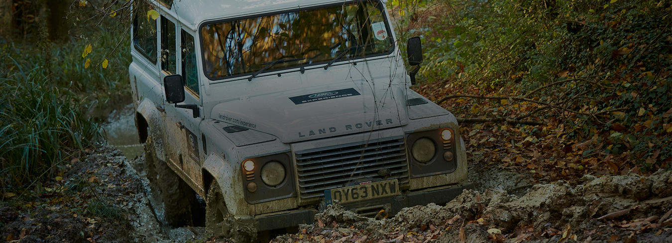 A photo of a land rover driving through the mud