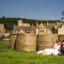 this is a photo of a bride and groom sitting infront of some hail bails with ellenborough park in the background