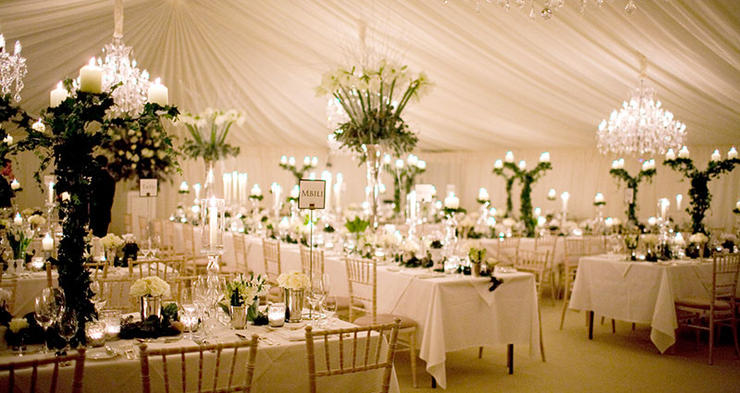a photo of a wedding reception in a white marquee