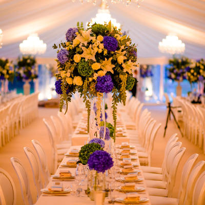 this is a photo of a long table with flowered centerpieces set up in a marquee