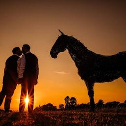 a photo of two grooms kissing next to the horse statue overlooking the sunset