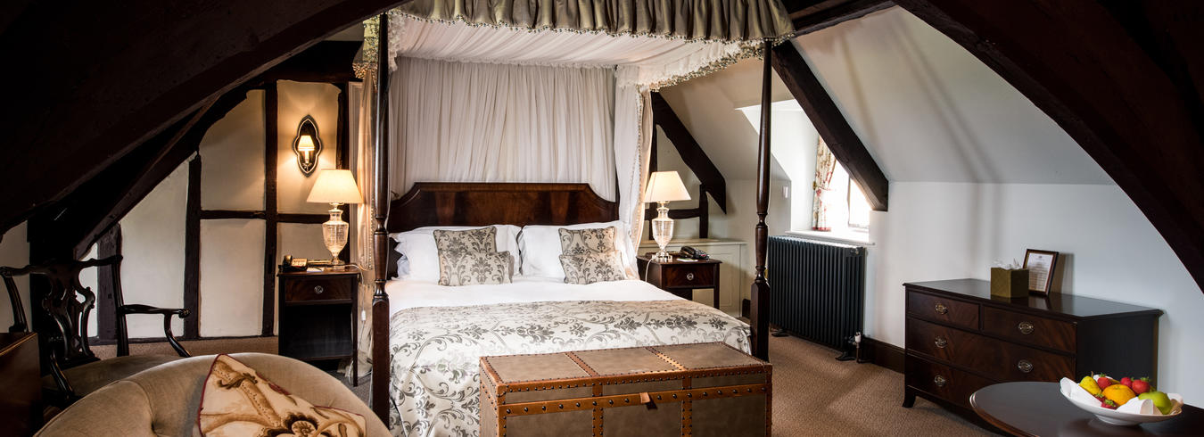 a photo of a luxury suite with a four poster bed