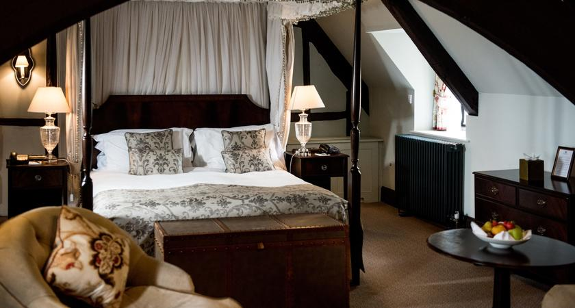 this is a phto of a suite with a four poster master bed with a living room