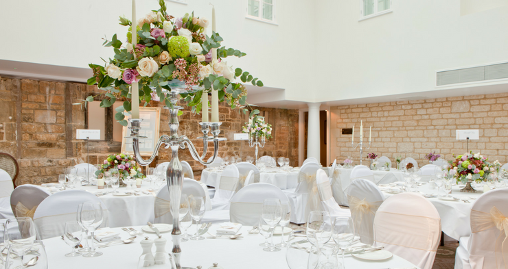 This is a photo of a wedding reception party set up in the hotel. All white theme with a colorful flower and candle mantelpiece