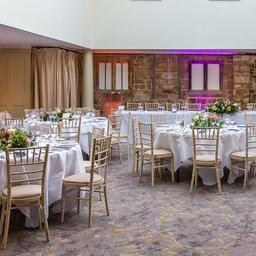 this is a photo of a wedding reception of white round tables set up with flower bouquets