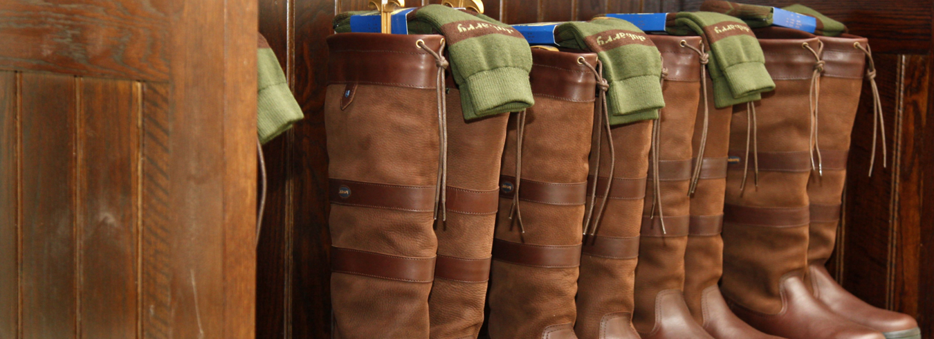 this is a photo of four pairs of brown leather wellies stacked up