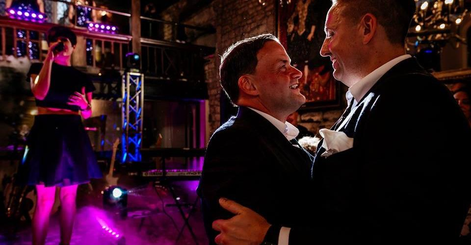 a photo of two grooms enjoying their first dance couple dancing